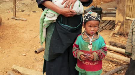 hill tribe : PONGSALI, LAOS - APRIL 2014: indigenous tribal native Akha woman carry baby in hill village