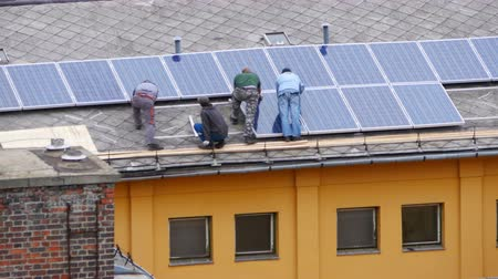 солнечный : worker installing solar panel roof top apartment