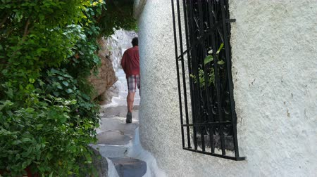 single man walking narrow streets of plaka, athens, greece, 4k