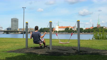 man swinging on swing, watching riga view, latvia Vídeos