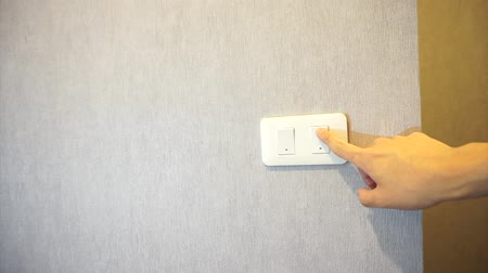 comutar : Man turning light on a wall switch