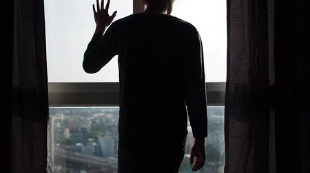 regret : Silhouette of man walking to window and looking out