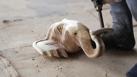 chisel : Traditional craftsman carving wood an elephant and sanding wood with motor sandpaper.