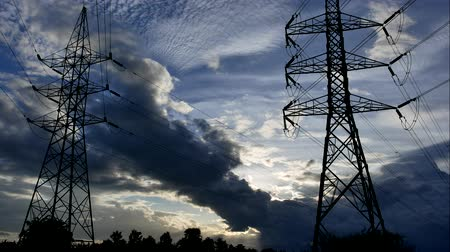karartmak : Time Lapse of Colorful dramatic sky with Silhouette of high voltage pole and sunset. Stok Video