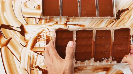 temper : Preparation of dark chocolate bars made from scratch using cocoa butter and sugar Stock Footage