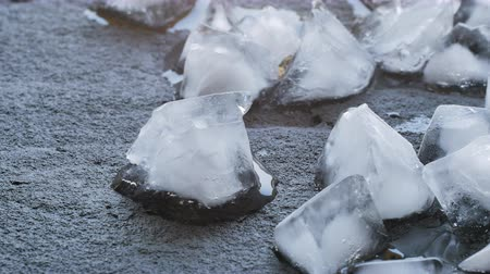 ice cube : Time Lapse Of Melting Ice Cubes on black stone in a hot day.