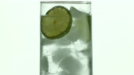Glass of sparkling water soda drink with ice and lime lemon slice rotating.