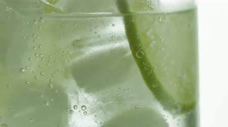 lemoniada : Glass of sparkling water soda drink with ice and lime lemon slice rotating.