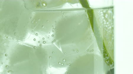 clear liquid : Glass of sparkling water soda drink with ice and lime lemon slice rotating.