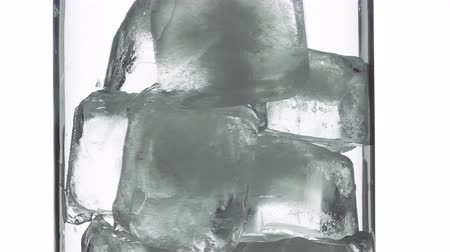 Put the ice cubes into the glass. Стоковые видеозаписи
