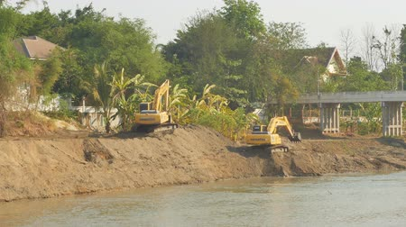 wysypisko śmieci : LAMPANG, THAILAND, MAY 3, 2019: Yellow Backhoes digging sand with shovels from the Wang River to support the water in the rainy season.