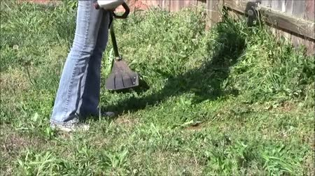 gramado : Teen girl using string trimmer  Stock Footage