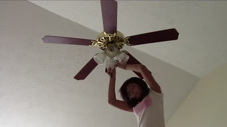 вентилятор : Teen girl changing light bulb in ceiling fan