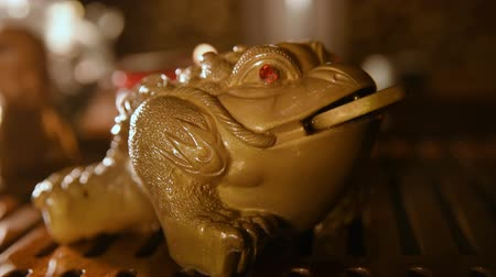 háromlábú : Tea figurine money toad changing color from water temperature.Slow motion