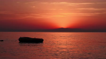 iluminado pelo sol : Beautiful red sunset over sea and silhouette of boat on water; Greece Stock Footage