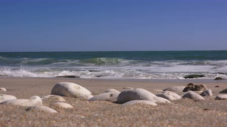 explodindo : Close up of sea pebbles against the backdrop of a stormy sea in sunny day Stock Footage