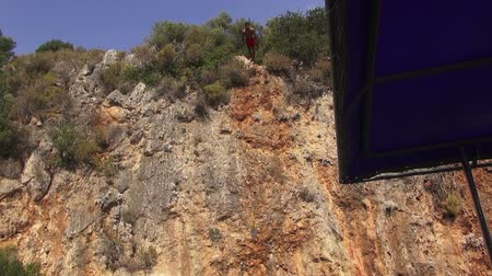 A man jumps from a cliff into the sea 05.10.2014, Turkey, Marmaris Stock mozgókép