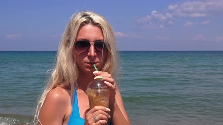 plastic cups : Blonde girl with long hair drinks coffee on the background of the sea
