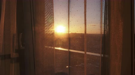 zonwering : View of the sunset from the window  through transparent curtain