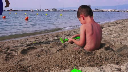 sea play : Young father with a small son on a sea beach is playing in the sand, Greece Stock Footage