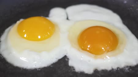 fried egg : Two eggs are fried in a frying pan in oil Stock Footage