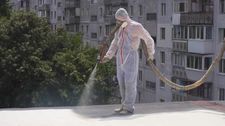 compressor : a man in a special form on the roof uses a chemical solution, painting the roof, insulates the roof Stock Footage
