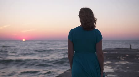 riviera : The lonely silhouette of a young girl in fluttering clothes is walking along the sea pier at dawn, against the rising sun Stock Footage