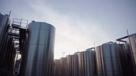Plant for the production of wine, large outdoor containers for wine, wine tanks. sunset.Rows of modern stell barrels in winemaker factory