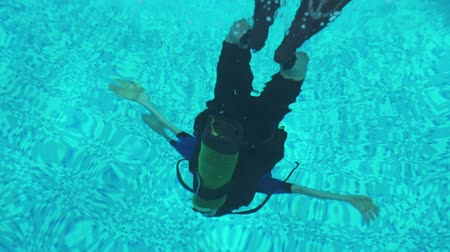 the diver trains to dive in the pool, swimming under water Stock mozgókép