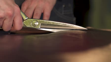 vágás : Women hands Cutting scissors cut the skin on the table, making leather goods