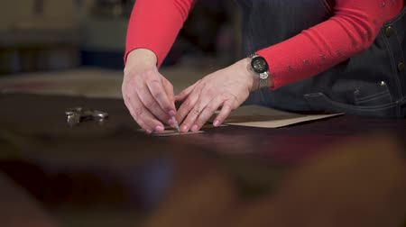 átadó : master marks the treated animal skin. He applies and tracks a cardboard template in a small craft workshop