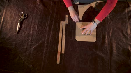 master marks the treated animal skin. He applies and tracks a cardboard template in a small craft workshop