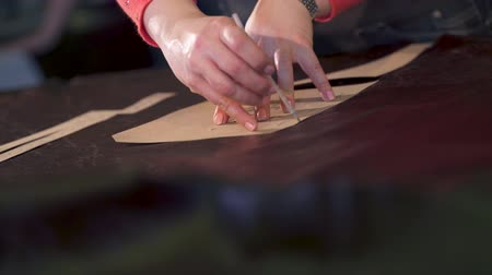 маркировка : master marks the treated animal skin. He applies and tracks a cardboard template in a small craft workshop