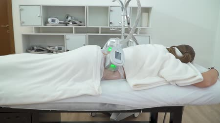 cryolipolysis, a woman is lying on the table during a procedure in a beauty parlor or spa center
