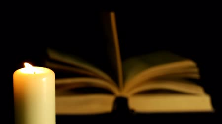 história : Candle blazes on background of the book