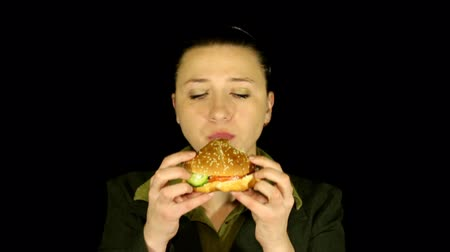 okurka : Woman on black background eats hamburger time lapse Dostupné videozáznamy