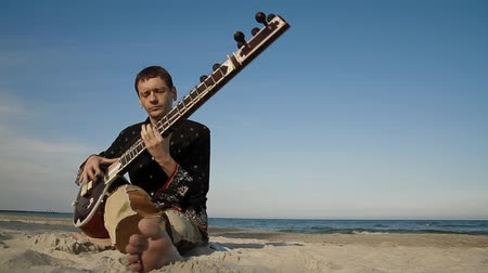 aktywność : Man plays the sitar on the beach