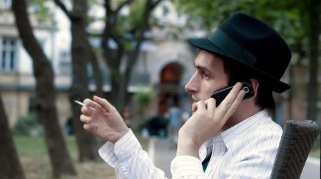 cigarettes : The smoking man on the phone in a cafe