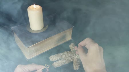 ведьма : Witch voodoo doll with a pin pierces in the smoke