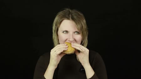 comer : Woman eating hamburger on a black background (timelapse) Vídeos