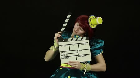 fosco : Woman clown plays with a movie clapperboard Stock Footage