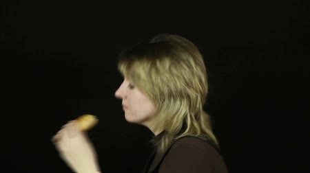 eat background : Woman eating hamburger on a black background (timelapse) Stock Footage