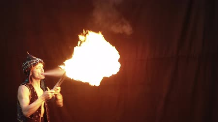 цирк : Fire breather on a black background