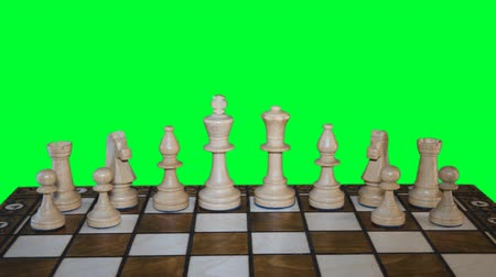 király : Chess figures form on chess board and prepare to battle on green-screen background