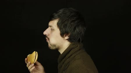 eat background : Man eating a hamburger on a black background