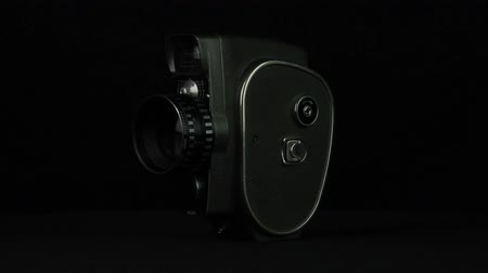 kino : 8 mm camera is rotated on a black background loop
