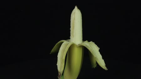 очищенные : Peeled banana rotates on a black background loop Стоковые видеозаписи