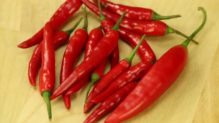chili : Hot peppers turns on wood background Stock Footage