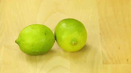 calcário : Two lime rotate on the background of wooden boards Stock Footage
