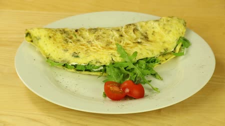 omlet : Omelet with herbs and tomatoes rotates on a wooden boards background Stok Video